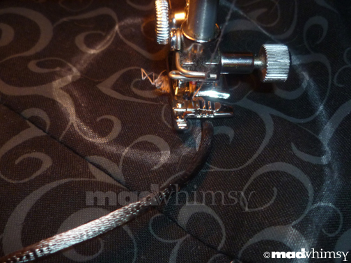 close-up of the fabric and satin cording being stitched together
